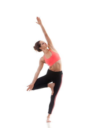 vriksasana: Sporty yoga girl on white background in vrikshasana (Vriksasana, Tree Pose)