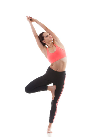 vriksasana: Sporty yoga girl on white background in vrikshasana (Vriksasana or Tree Pose) Stock Photo