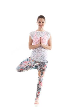 vriksasana: Smiling yoga girl on white background in vrikshasana (Vriksasana or Tree Pose) using namaste