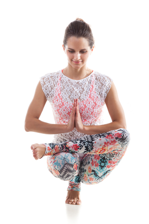 Smiling yoga girl on white background squatted down with palms touching in a gesture of namaste