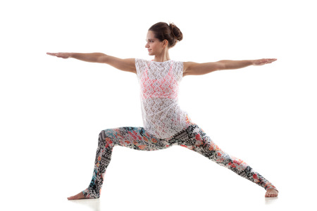 warrior pose: Smiling yoga girl on white background in virabhadrasana 2 (Warrior 2 Pose)