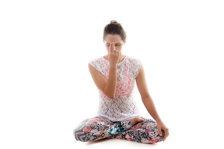 Yoga girl on white background practicing nadi shodhana pranayama (Alternate, Nostril, Breathing) photo