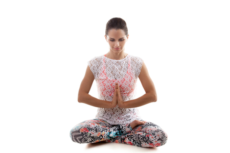 anjali: Yoga girl on white background in sukhasana (Easy Pose, Decent Pose, Pleasant Pose) bows