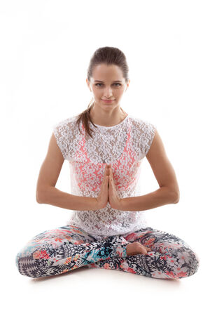 anjali: Yoga girl on white background in sukhasana (Easy Pose, Decent Pose, Pleasant Pose) vertical Stock Photo