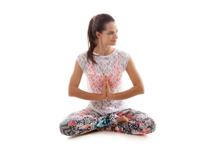anjali: Smiling Yoga girl on white background in sukhasana (Easy Pose, Decent Pose, Pleasant Pose) Stock Photo