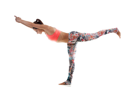 Yoga girl on white background is standing on one foot and stretching another photo
