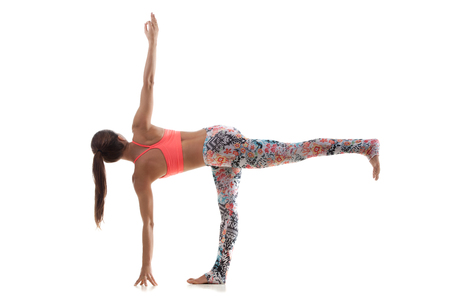chandrasana: Yoga girl on white background in parivritta ardha chandrasana (Revolved Half Moon Pose) Stock Photo