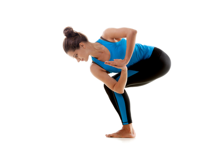 Sporty yoga girl on white background bending looks down