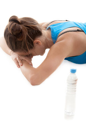 lies down: Sporty yoga girl on white background lies down resting near the bottle of water