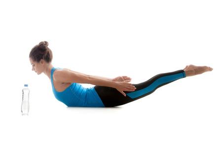 poses de modelos: Ni�a de yoga deportivo en el fondo blanco practicando extensi�n hacia atr�s de la columna vertebral, cerca de la botella de agua