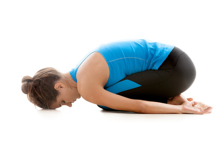 mediate: Sporty yoga girl on white background relaxing after practice Stock Photo