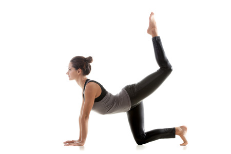 Sporty yoga girl on white background doing exercises for buttocks photo