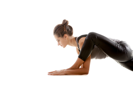 bent over: Sporty yoga girl on white background exercises, the left knee is bent over the left ankle close-up