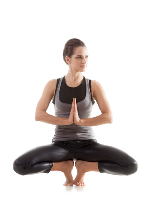 anjali: Sporty yoga girl on white background sitting in squatting position with palms in Anjali mudra Stock Photo