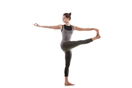 big toe: Sporty yoga girl on white background in parivritta hasta padangushthasana (Extended hand to big toe pose) Stock Photo