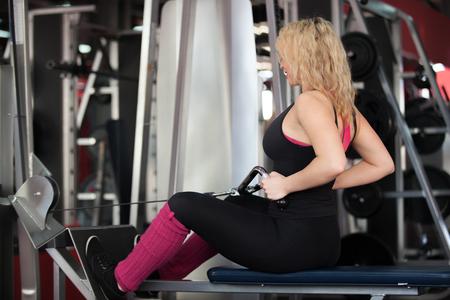latissimus: Cliente femminile della palestra in sportswear facendo esercizi per i muscoli della schiena, basso gran dorsale sulla seduta macchina fila cavo (la forma vista posteriore)