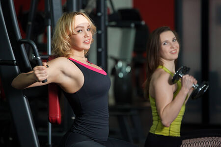 animal practice: Two sporty girlfriends in sportswear do weight training for arms and chest in fitness center