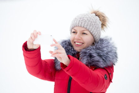 Happy beautiful girl in knitted hat and red winter coat using mobile phone, taking picture with smartphone outdoors against the snow photo