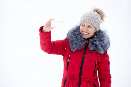 Happy beautiful girl in knitted hat and red winter coat using smart phone, taking picture with smartphone outdoors against the snow photo