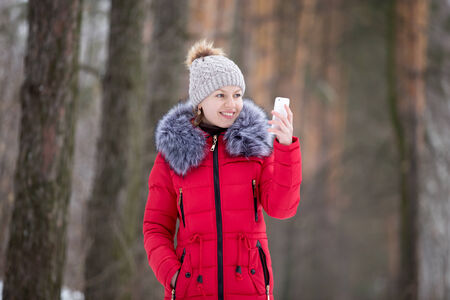 Happy beautiful girl in knitted hat and red winter coat, outdoors, using mobile phone, looks on the screen of smart phone photo