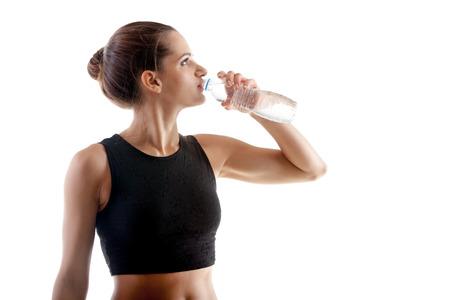 mujeres fitness: Ni�a de yoga deportivo en el fondo blanco agua potable despu�s de la pr�ctica Foto de archivo