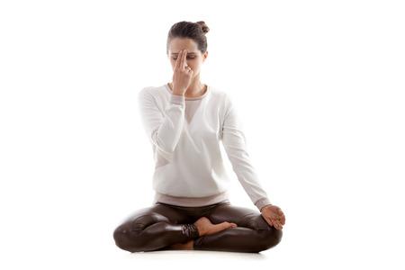 persona respirando: Muchacha de la yoga en el fondo blanco practicando pranayama shodhana nadi (Suplente, ventana de la nariz, la respiraci�n) en posici�n de loto