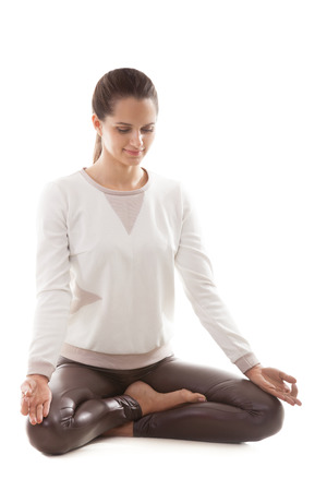 sukhasana: Yoga girl on white background in sukhasana (Easy Pose, Decent Pose, Pleasant Pose) Stock Photo