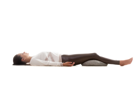 Yoga girl on white background lying in Shavasana (Savasana, Corpse Pose)