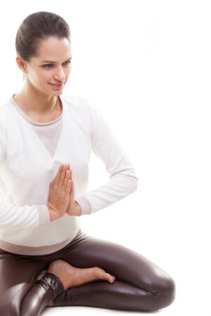sukhasana: Yoga girl on white background in sukhasana (Easy Pose, Decent Pose, Pleasant Pose) with palms in namaste Stock Photo
