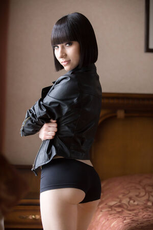 leather coat: Beautiful smiling sexy girl in black leather jacket and shorts, caucasian model in bedroom