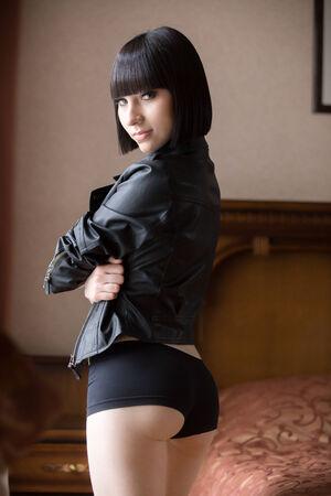 ropa interior ni�as: Sonriente hermosa chica sexy en la chaqueta de cuero negro y pantalones cortos, modelo cauc�sico en el dormitorio