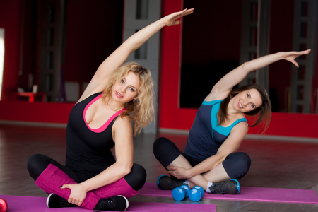 plus size woman: Two pretty girls do aerobic exercises, side body bending on mats in sports hall