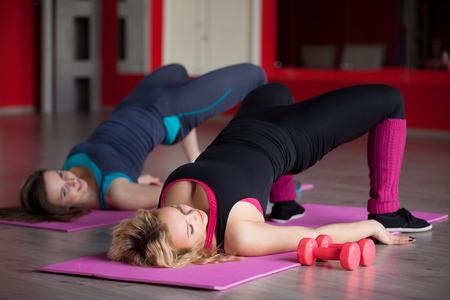 aerobics: Dos muchachas bonitas que hacen ejercicios aer�bicos para las caderas y las nalgas en posici�n acostada sobre esteras en el gimnasio Foto de archivo