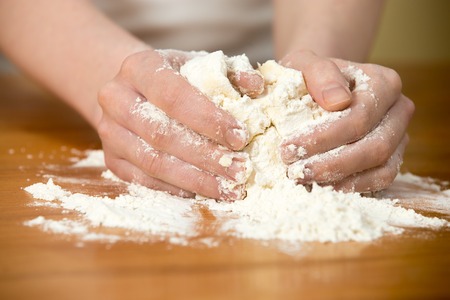 p�trir: Close up homemade cooking, female hands knead paste on wooden table Banque d'images