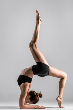 Beautiful sporty yogi girl practices yoga asana, handstand with bending, standing on forearms, standing on elbows photo