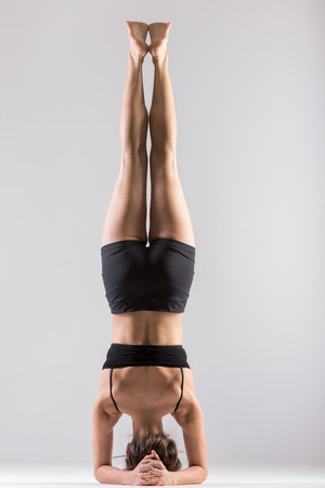 headstand: Sporty girl doing Supported Headstand, yoga asana Sirsasana, Shirshasana, Sirshasana, Headstand on grey background, low key shot Stock Photo
