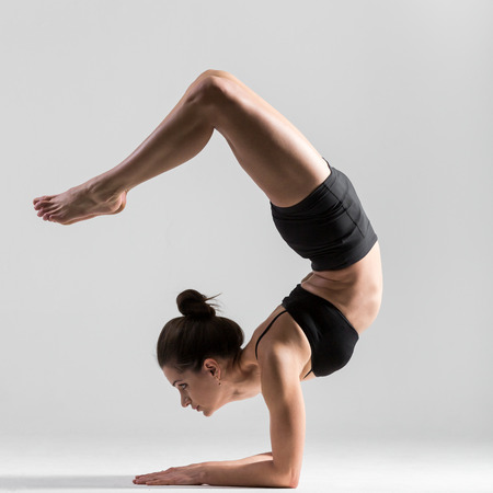Mooie sportieve yogi meisje yoga asana, Pincha mayurasana, voorarm tribune, gevederde pauw pose, elleboog balans