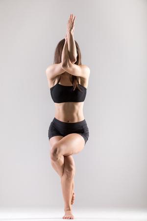 Beautiful sporty yogi girl practices yoga asana, Garudasana,Eagle Pose on grey background, low key shot photo