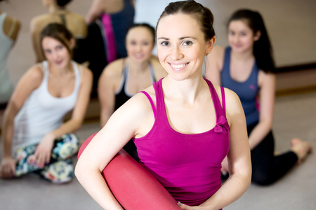 Happy yogi girl holding folded pink yoga mat, her class partners sitting on the background photo