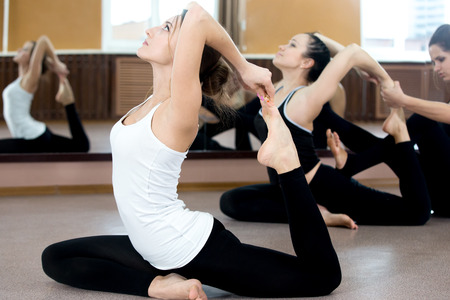 aerobics: Girls doing yoga exercises in class, sitting in asana eka pada radzhakapotasana (One-Legged King Pigeon Pose) - hands grasps feet, instructor on the background coaching one of the yoga students