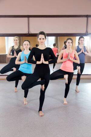 vriksasana: Sporty yogi girls in class in Yoga pose vrikshasana (Vriksasana or Tree Pose) using Namaste (full length)