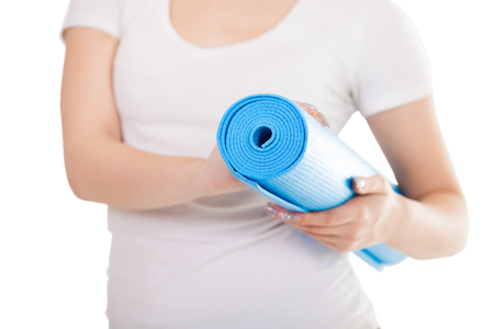 keep fit: Close up, white woman hands holding folded blue yoga, pilates mat, ready for fitness exercises. Healthy life, keep fit concepts. Isolated on white background Stock Photo