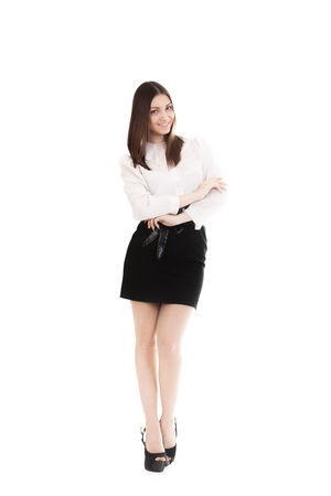 Office employee, beautiful young woman in office uniform, black skirt and white shirt friendly smiling, isolated, full length