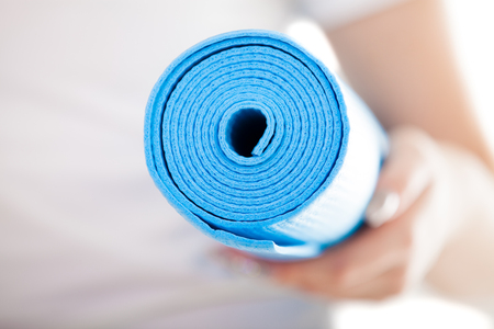arm up: Close up, white woman hands holding folded blue yoga, pilates mat for fitness training. Healthy life, keep fit, weight loss concepts. Focus on mat, white t-shirt on background