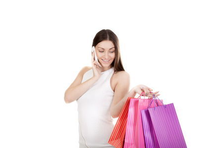 blissfully: Happy female in white dress shopping, blissfully looking on colored paper bags in her hand, talking on the cell phone, holding smartphone, making call. Isolated on white background