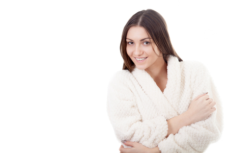 to muffle: Beautiful young woman muffle, wrap herself up in white bathrobe, isolated, white background. Cozy, comfort, wellbeing, healthcare, bodycare concepts