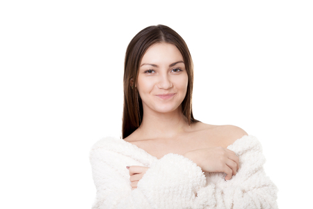 Portrait of smiling sexy young woman taking off white bathrobe, undress exposing shoulders, with provocative look, isolated on white background Stock Photo