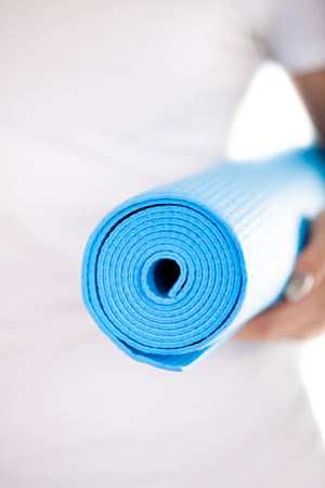 keep fit: Close up, white woman hands holding folded blue yoga, pilates mat, ready for fitness exercises. Healthy life, keep fit concepts. Focus on mat, white t-shirt on background Stock Photo