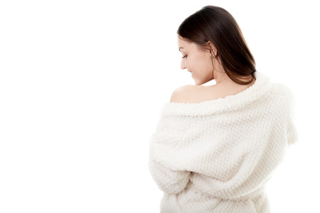 undress: Beautiful sexy young woman in white bathrobe undress exposing one shoulder, isolated, copy space. Cozy, beauty, comfort, wellbeing, healthcare, bodycare concepts