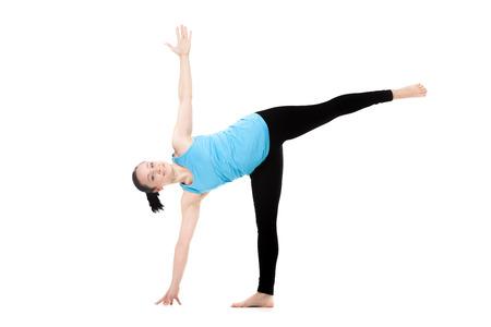 Yogi girl on white background exercises in yoga posture ardha chandrasana (Half Moon Pose)